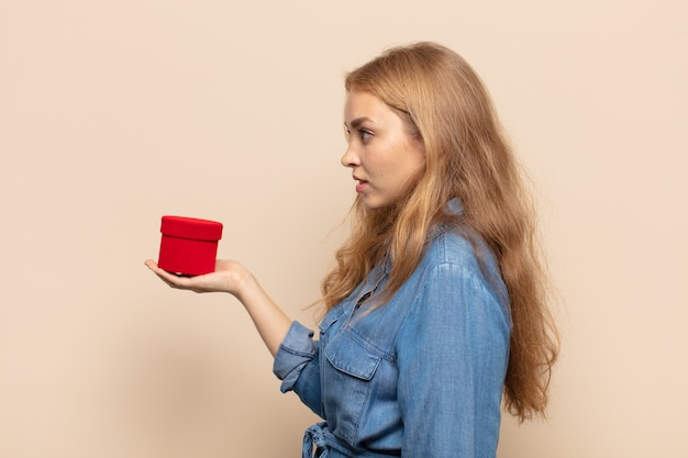 Femme blonde sur la vue de profil à la recherche d'avance, de penser, d'imaginer ou de rêver