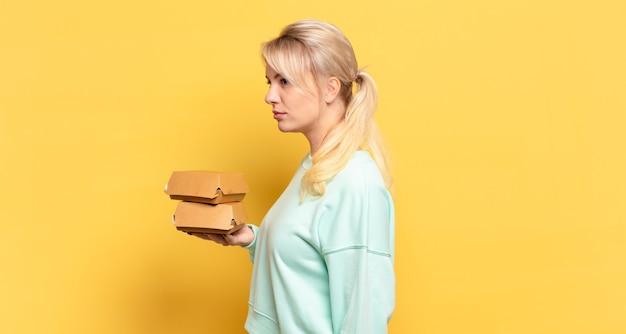 Femme blonde sur la vue de profil à la recherche de copier l'espace à venir, penser, imaginer ou rêver