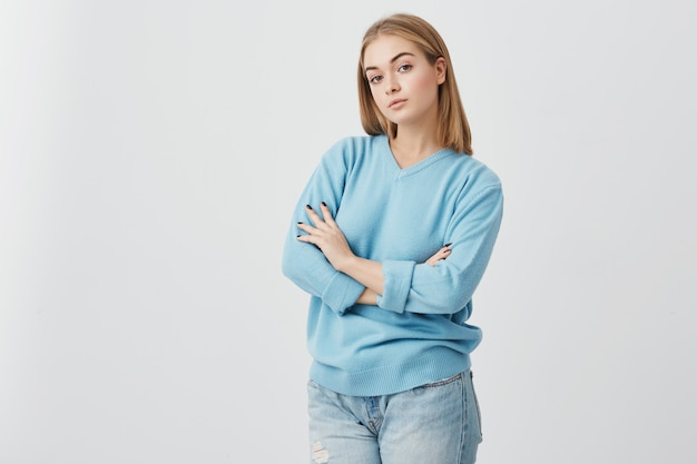 Femme blonde avec des yeux sombres et chauds et une peau saine, debout avec les bras croisés, regardant directement dans la caméra. séduisante fille avec une belle apparence habillée avec désinvolture posant en studio.
