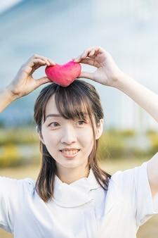 Une femme en blouse blanche avec un accessoire en forme de coeur