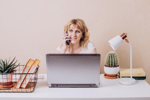 Une femme en blouse blanche est assise devant un ordinateur portable et parle au téléphone travail à distance et apprentissage en ligne