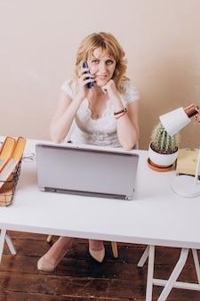 Une femme en blouse blanche est assise devant un ordinateur portable et parle au téléphone
