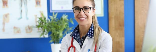 Femme en blouse blanche et avec un stéthoscope rouge autour de son cou s'asseoir avec ses mains jointes à table.