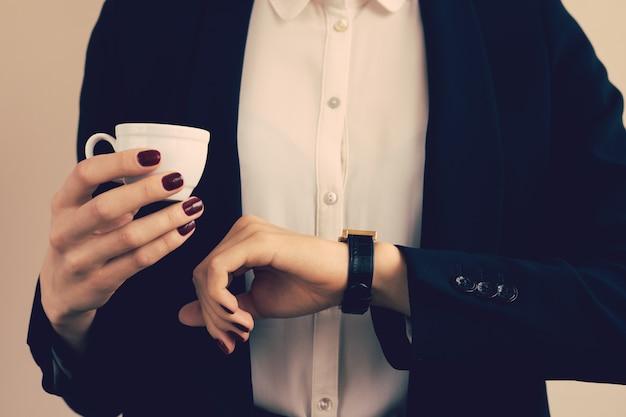 Femme en blouse blanche et veste noire tenant une tasse de café et regardant l'horloge