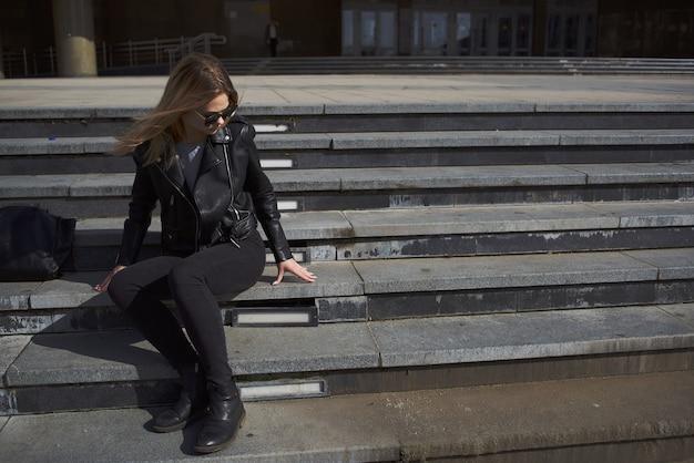 Femme en blouson de cuir près du bâtiment en plein air vacances été