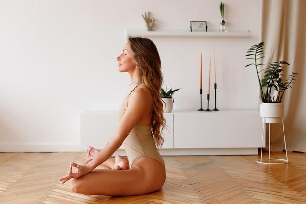 Une femme en body en posture de lotus médite à la maison