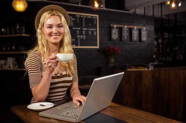 Femme, boire, café, utilisation, ordinateur portable