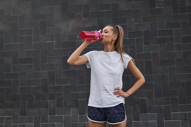 Femme boire de l'eau bouteille rouge après l'entraînement du matin