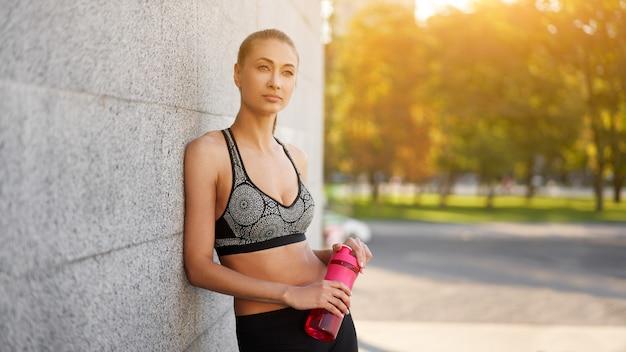 Femme boire de l'eau bouteille rouge après la scène de la ville d'entraînement du matin
