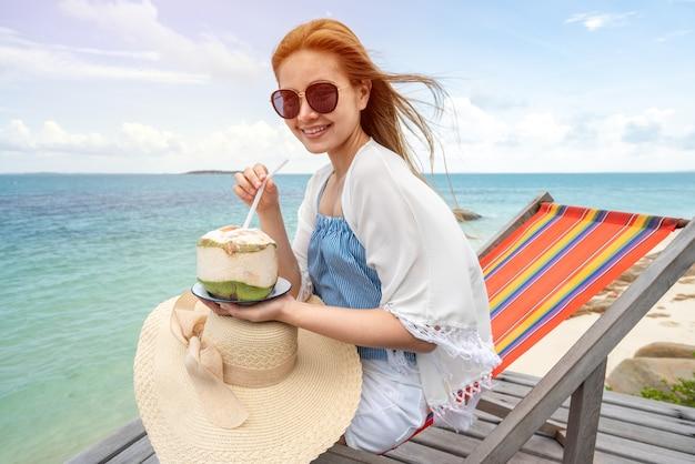 Femme, boire une eau de coco sur une chaise confortable sur la plage