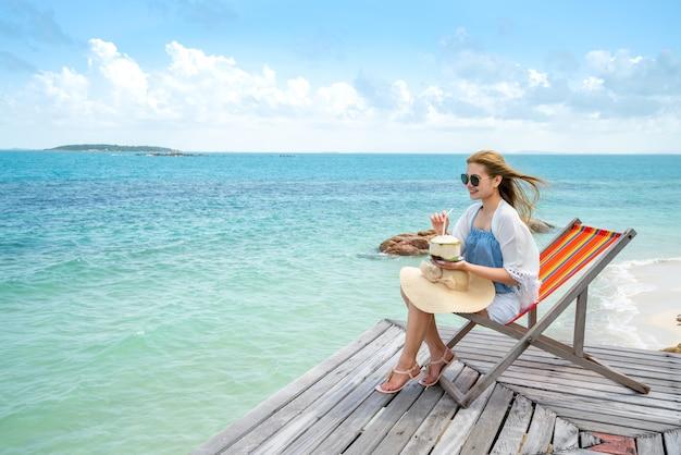 Femme boire une eau de noix de coco sur une chaise confortable sur la plage, copie espace.