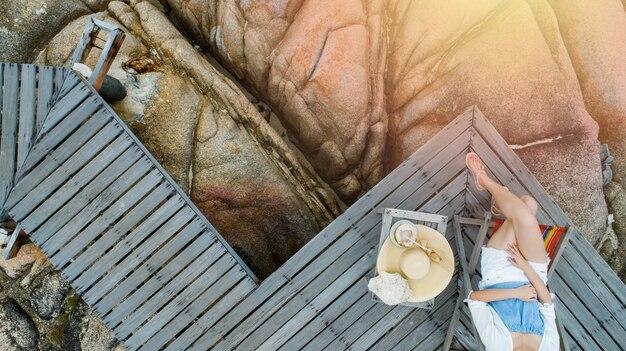 Femme boire une eau de noix de coco sur une chaise confortable sur la plage, espace de copie