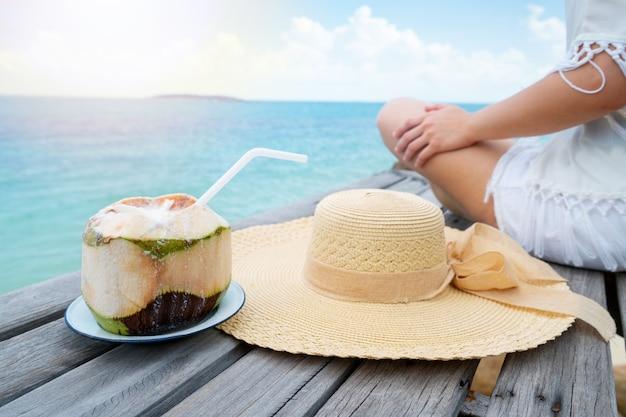 Femme boire une eau de smoothie de noix de coco sur une chaise confortable sur la plage, espace copie.