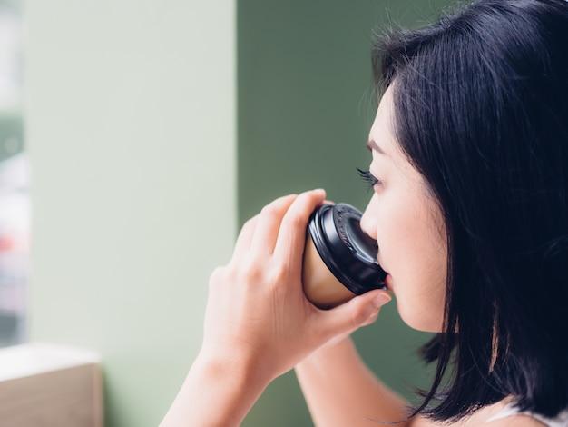 Femme boit du café par les fenêtres
