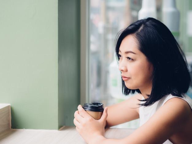 Femme boit du café par les fenêtres.
