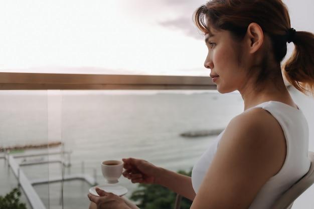 Une femme boit du café et se détend sur le balcon avec vue sur la mer
