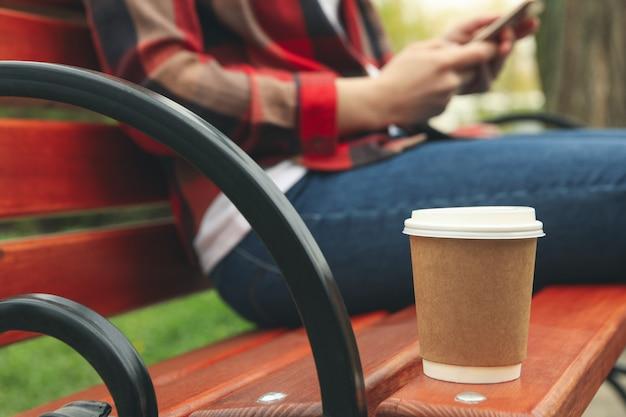 Femme boit du café et utilise un smartphone dans le parc. heure du déjeuner