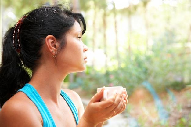 La femme boit du café.