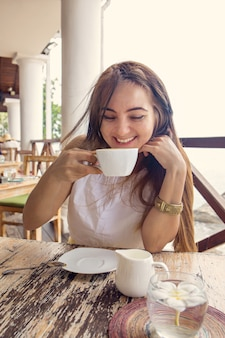 Une femme boit du cappuccino