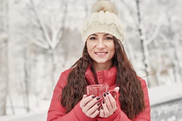 Femme boit du thé chaud ou du café de tasse à cozy snowy house garden le matin d'hiver. belle femme appréciant l'hiver à l'extérieur avec une tasse de boisson chaude. vacances de noël. mode de vie d'hiver confortable.