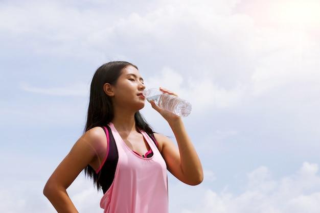 La femme boit de l'eau de la bouteille en raison de la déshydratation de la chaleur
