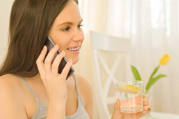 Femme boit de l'eau avec du citron, parlant au téléphone