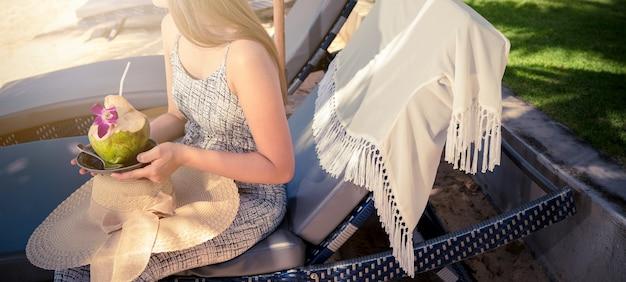 Femme boit une eau de noix de coco sur une chaise confortable