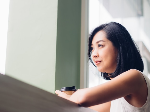 Une femme boit une tasse de café au café.