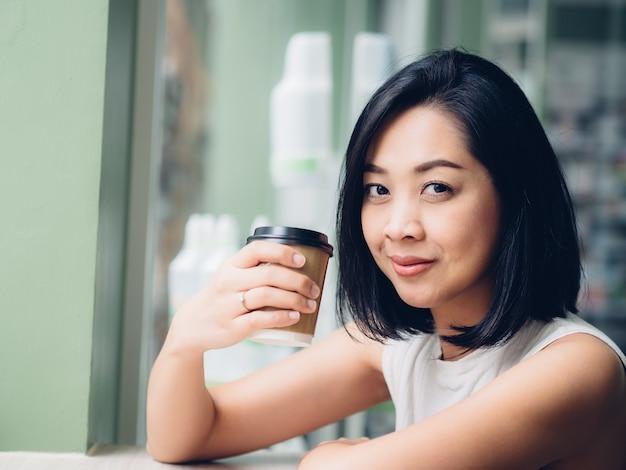 Femme boit une tasse de café chaud dans le café.