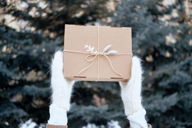 Femme avec boîte cadeau ou cadeau à l'extérieur. mains en mitaines tricotées. porter des vêtements chauds élégants