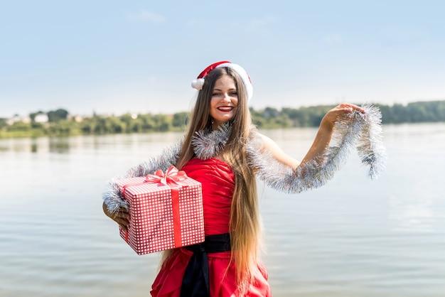 Femme avec boîte-cadeau et guirlande posant sur le rivage