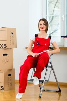 Femme avec boîte de déménagement dans sa maison