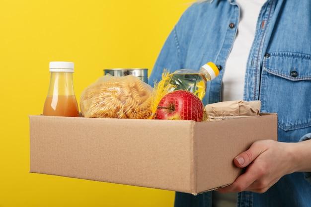 Femme avec boîte de dons sur espace jaune. faire du bénévolat