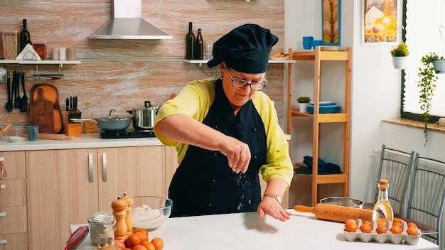 Femme avec bonete tamisant la farine sur une table en bois prête pour la cuisson. boulanger senior à la retraite avec tablier, uniforme de cuisine saupoudrant, tamisant, étalant les ingrédients rew à la main en cuisant du pain fait maison.