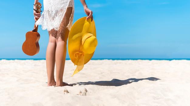 Femme de bonheur implantation sur la plage lever les mains au ciel bleu