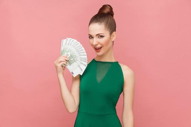 Femme de bonheur tenant beaucoup d'euro