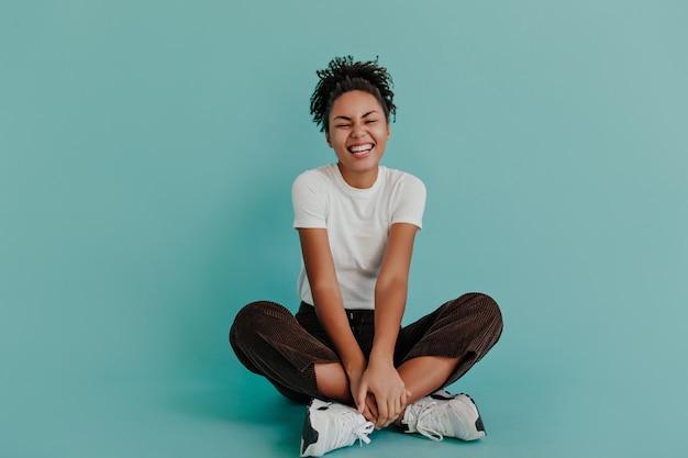 Femme de bonne humeur assise avec les jambes croisées