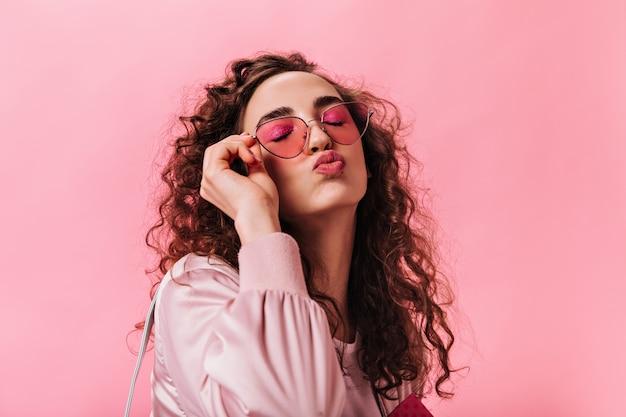 Femme de bonne humeur enlève ses lunettes de soleil roses et souffle baiser