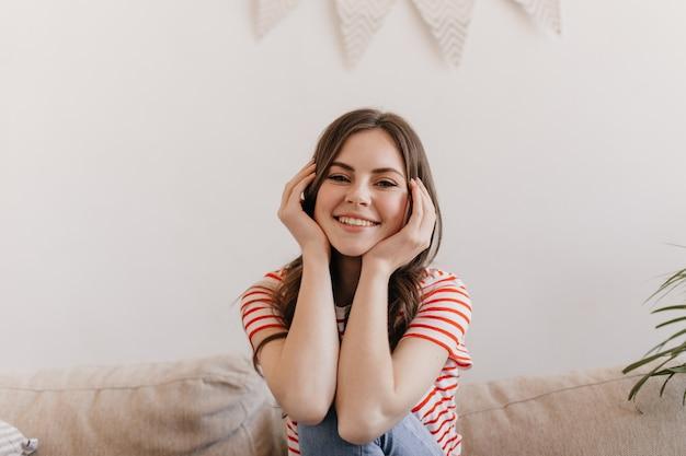 Femme de bonne humeur regarde à l'avant et pose assis sur un canapé dans le salon