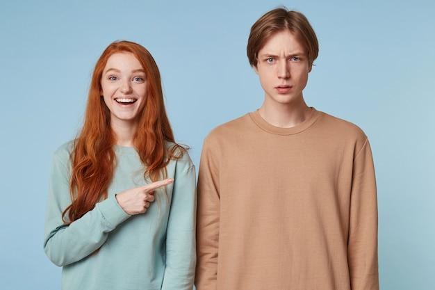 Femme de bonne humeur, sourires joyeux, montre du doigt le gars qui se tient avec une expression faciale suspecte confuse et incompréhensible