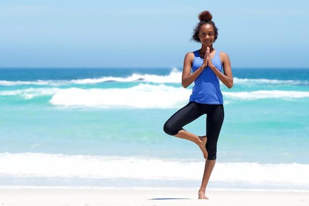 Femme en bonne santé, faire des exercices d'yoga à la plage