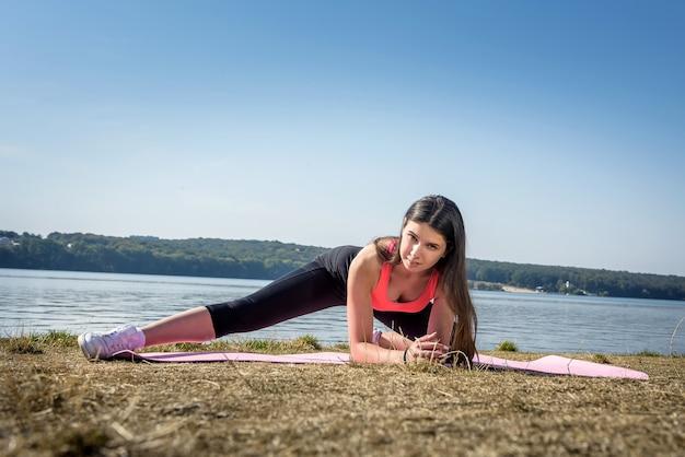 Femme en bonne santé se reposant et faisant des exercices d'étirement en plein air près du lac.