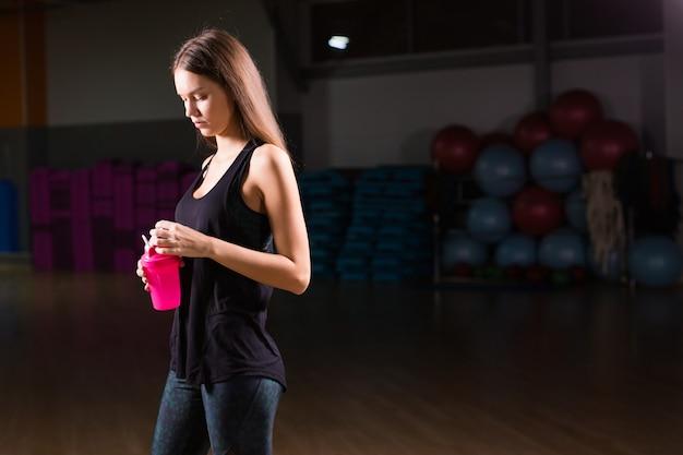 Femme en bonne santé avec sport shake protéiné dans la salle de gym