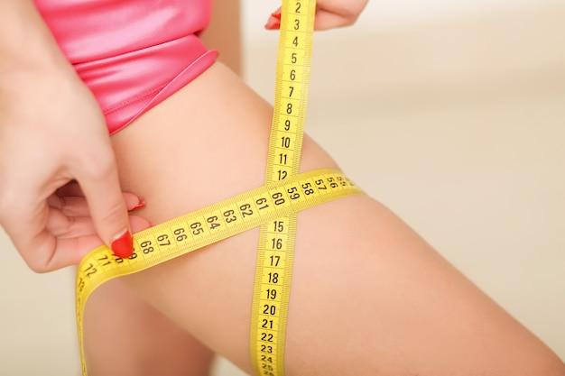Femme en bonne santé, sportive et en maillot de bain. belle fille mesurant son corps