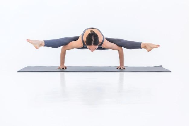 Femme en bonne santé sportive pratiquant le yoga faisant le poirier de ficelle pose sur tapis sur fond blanc