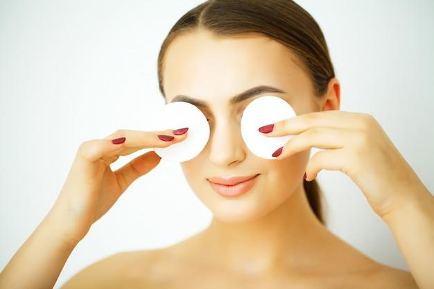 Femme en bonne santé avec des tampons de coton blancs. concept de traitement hygiénique, nettoyant et facial