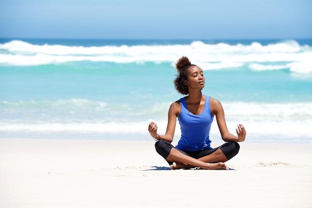 Femme en bonne santé yoga jeune méditant à la plage