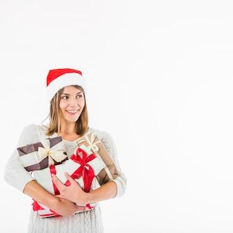 Femme en bonnet de noel avec coffrets cadeaux