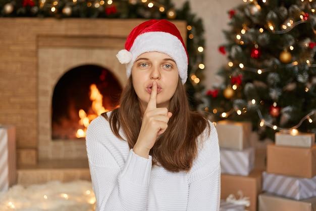 Femme avec bonnet de noel faisant un geste calme et en gardant le doigt près des lèvres, fille aux cheveux raides posant dans le salon avec arbre de noël et cheminée.