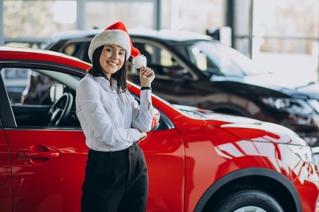 Femme en bonnet de noel à noël dans la salle d'exposition de voiture
